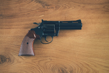 Revolver handgun on the wooden background