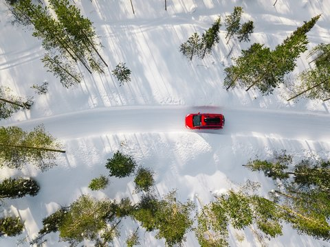 Aerial view of red car driving through the white snow winter forest on country road in Finland, Lapland.