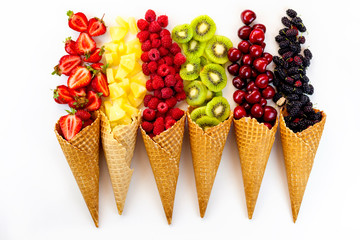 Scattered fruits (strawberries, pineapple, raspberries, kiwi, blackberries, cherries) in waffle, cone cups on  a whait background; toned