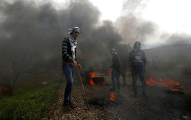 Palestinian demonstrators are seen during clashes with Israeli forces at a protest in al-Mughayer village near Ramallah, in the Israeli-occupied West Bank