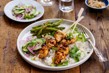 Satay chicken skewers with pickled cucumber salad