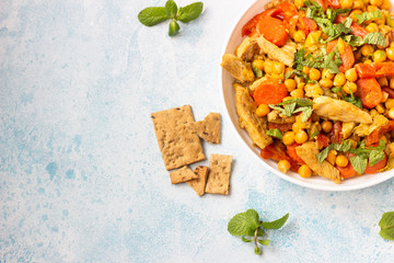 Curry with chickpea, turkey, carrot, leek and dried apricots in a white plate. Healthy food. Concrete background. Copy space.