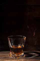 close-up view of whiskey in glass and reflection on wooden table