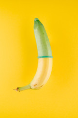 Tuinposter Akt Banana with green condom in front of yellow background
