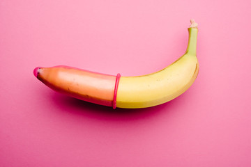 Fotorolgordijn Akt Pink condom on banana in front of pink background