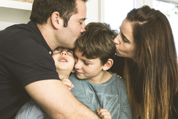 Portrait of a happy family kissing and hugging at home. Family lifestyle showing affection