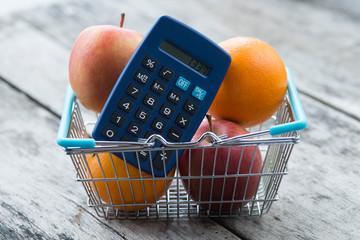 Einkaufskorb mit Obst und Taschenrechner