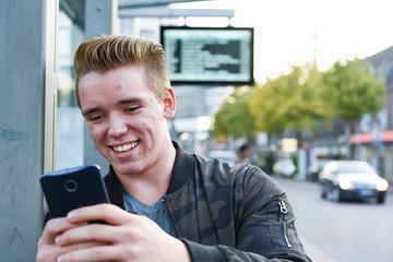 Jugendlicher mit Smartphone in der Stadt