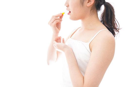 薬・サプリメントを飲む若い女性