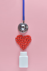 A heart shape of medicine pills pouring out of white bottle and stethoscope on pink background. Concept of Valentine's Day or pharmacy, Medical.