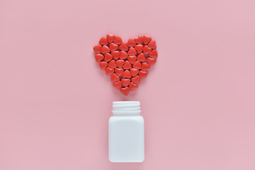 A heart shape of medicine pills pouring out of white bottle on pink background. Concept of Valentine's Day or pharmacy, Medical.