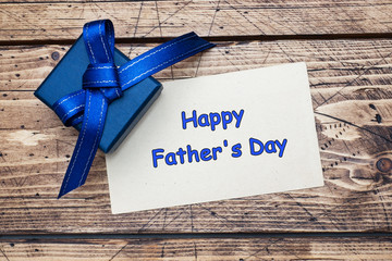 Blue gift box with ribbons and space for text on wooden table. Father's Day Concept.