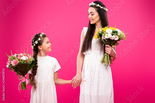 9a40c34db6 beautiful happy mother and daughter in white dresses and floral wreaths  holding bouquets and smiling each