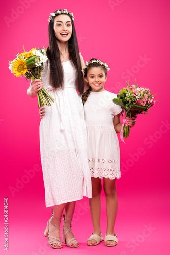 99e229bec4 happy mother and daughter in white dresses and floral wreaths holding  beautiful bouquets on pink