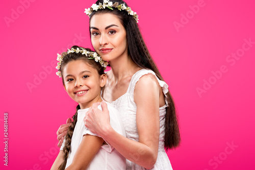 49e955ccfc beautiful happy mother and daughter in white dresses and floral wreaths  smiling at camera isolated on