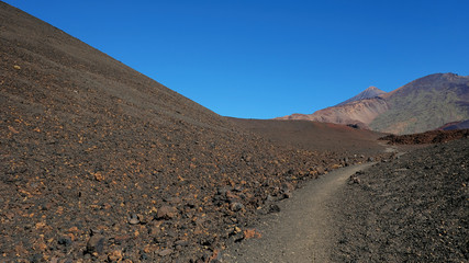 Path through the lunar landscape of Montaña Samara in Teide National Park, one of the most alien-like, volcanic land in Tenerife with views towards Pico del Teide, Pico Viejo, and Las Cuevas Negras