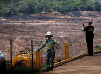 A federal police officer takes picture of the collapsed Brazilian mining company Vale SA, in Brumadinho