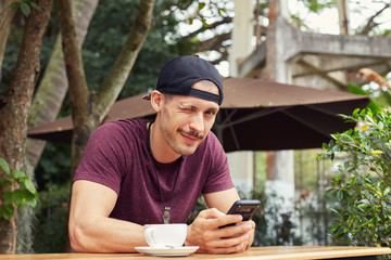 Young Caucasian man wearing pink t-shirt and hat, sitting at the cafe table with cup of coffee, swapping pics, remembering student life, while waiting for university mate against wooden background.