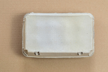 Top view of cardboard egg container on a brown background