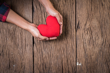 Hand holding red heart on wood background