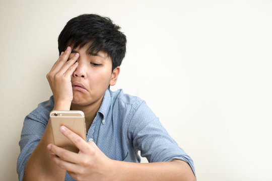 The only sad person is watching bad news from a mobile phone.