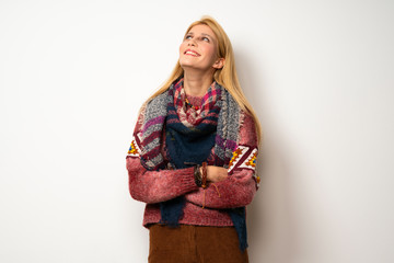 Hippie woman over white wall looking up while smiling