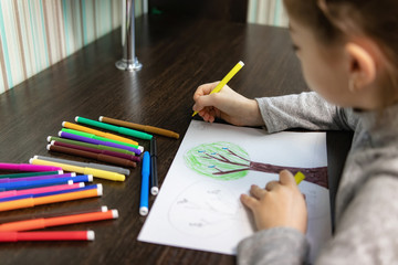 A 9-year-old girl draws a picture with colored markers with trees and birds