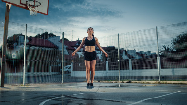 Beautiful Energetic Fitness Girl Skipping/Jumping Rope. She is Doing a Workout in a Fenced Outdoor Basketball Court. Evening Shot After Rain in a Residential Neighborhood Area.