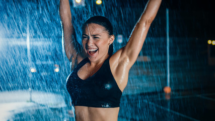 Beautiful Sporty Fitness Girl is Celebrating Her Athletic Accomplishments. She is Cheering at Night in Heavy Rain with One Light Behind Her.