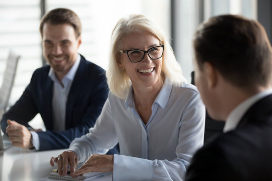 Friendly middle aged female leader laughing at group business meeting, happy old businesswoman enjoying fun conversation with partner, smiling mature business coach executive talking to colleague