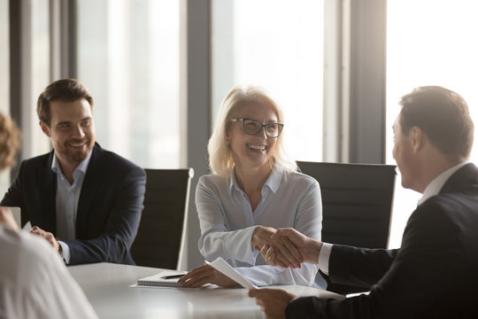 Happy mature businesswoman handshaking new male partner, ceo and smiling middle aged lady shaking hands at group meeting making deal, rewarding or hiring, celebrating business contract with client