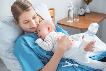 high angle view of smiling young mother holding baby bottle with milk and lying in bed with adorable baby