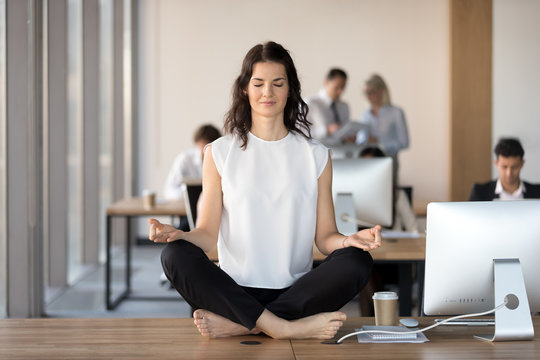Calm young business woman doing yoga exercise at workplace sitting at work desk in lotus position, peaceful female employee office worker meditating relaxing taking break for stress relief concept