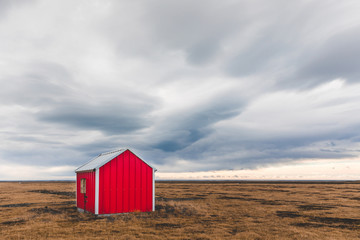 Small lone barn in Iceland with dramatic clouds in the sky