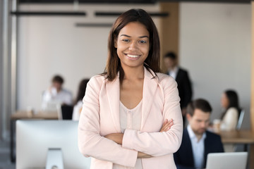 Smiling millennial african american corporate employee executive, mixed race office worker or team leader looking at camera, female young black professional business coach company manager portrait Fotobehang