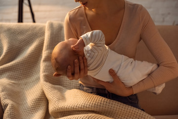 cropped shot of young mother holding baby during breastfeeding at night