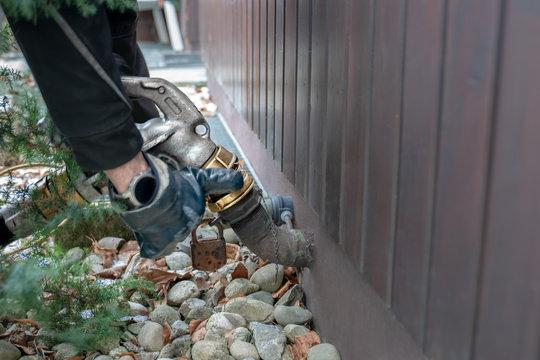 Detailaufnahme eines Lieferanten. Der Mann trägt Handschuhe und befestigt einen Schlauch für die Heizöl Lieferung. Der Schlauch befördert das Öl in den Tank im Haus für die Heizung.