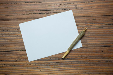 cannabis cigarettes on wood background.