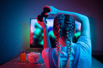 Gamer or streamer girl at home in a dark room with a gamepad, playing with friends online in video games. with popcorn and multicolored light