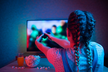 Gamer or streamer girl at home in a dark room with a gamepad, playing with friends online in video games. with popcorn and multi-colored light. Background