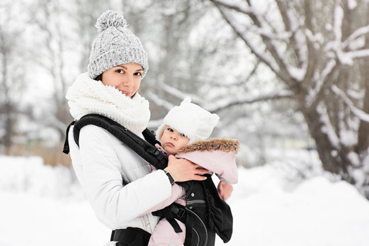 Little baby girl and her mother walking outside in winter Mother is holding her baby babywearing in the ergo carrier