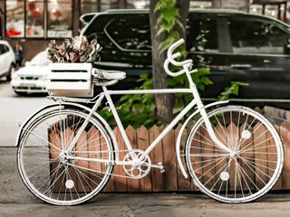 Painted white bike on street of European city near road with cars