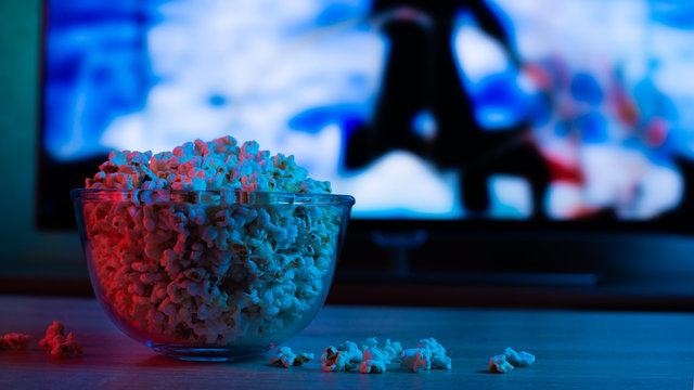 Popcorn in a glass plate on the background of the TV. Color bright lighting, blue and red. Background