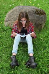 Teen girl wearing eyeglasses, jeans, red plaid shirt and black boots sitting against big stone on green meadow grass reads book and learning for exams. Education and leisure concept.