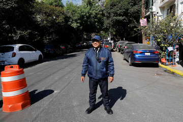 A security guard keeps watch at a street following an earthquake in Mexico City