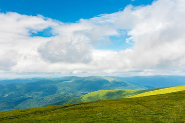 landscape in mountains. hills and meadows. sunny weather with beautiful cloudscape. grassy green slope and distant ridge.