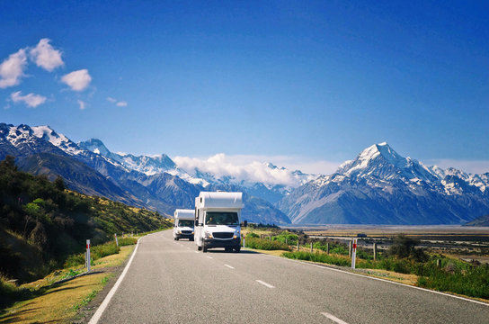 Two white caravan cars on the way in New Zealand. Traveling concept. Camper vans.