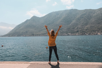 life style. travel and freedom. Hands up. Girl on the background of the mountains of Montenegro is standing, jumping in the old town by the sea