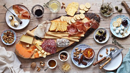 Appetizers table with various of cheese, curred meat, sausage, olives and nuts Festive family or party snack concept. Overhead view.