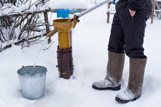 A frozen man in felt boots pours clean drinking water into a bucket using a water pump, against the backdrop of a snow-covered garden, on a cold winter evening in the village.